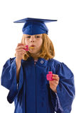 Young Graduate. A young graduate in her cap and gown, blowing bubbles and dripping bubbles down her graduation gown. Isolated on white, vertical layout with copy Royalty Free Stock Photo