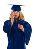 Young Graduate. A young graduate in her cap and gown, blowing bubbles and dripping bubbles down her graduation gown. Isolated on white, vertical layout with copy Royalty Free Stock Image