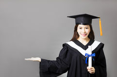young  graduate holding diploma with showing gesture Royalty Free Stock Images