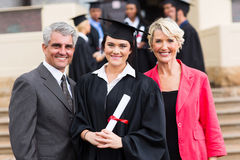 Young graduate parents. Pretty young graduate with happy parents at graduation ceremony Stock Photo
