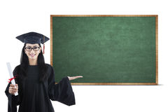 Young graduate showing empty board Royalty Free Stock Image