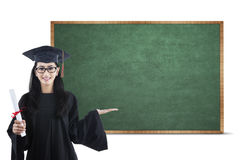 Young graduate showing empty board 1 Stock Photography