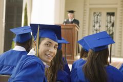 Young Graduate Student Attending Graduation Ceremony. Portrait of young male graduate with friends attending graduation ceremony Royalty Free Stock Photo