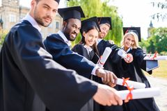 young graduated students holding stock image