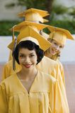 Young Graduates Standing In A Row. Portrait of happy young graduates standing in a row Royalty Free Stock Images