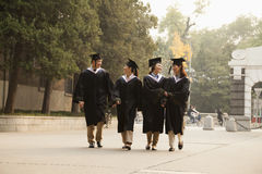 Young Graduates Walking Across Campus Royalty Free Stock Photos