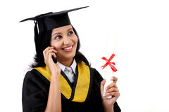 Young graduation female student talking on mobile phone Stock Images