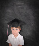 Young Graduation Student and Chalk Board. A young boy is wearing a graduation cap and tassel against a black chalk board. Add your text to the copyspace. Use it Stock Photography