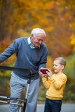 Young grandson showing something on phone to grandfather Royalty Free Stock Photography