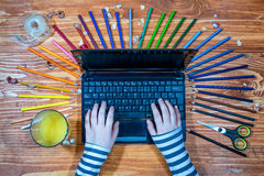 Young graphic designer with laptop and color palette. Young graphic designer with laptop and color pencils on a wooden table stock photos