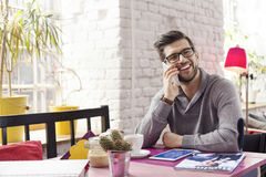 Young graphic designer with phone. In creative interior stock images