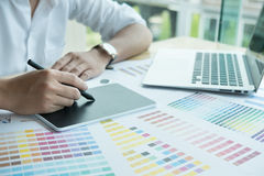 Young graphic designer working with computer and color swatch. c. Young male graphic designer working with computer and color swatch. creative man using stylus royalty free stock photos