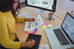 Young graphic designer working at office desk. High angle view of young graphic designer working at office desk Royalty Free Stock Images
