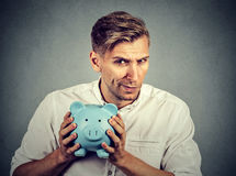 Young greedy stingy business man holding piggy bank. Greedy stingy business man holding piggy bank isolated on gray wall background Stock Photos
