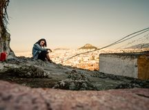 Young Greek girl on the background of the panorama of the city in the tourist area of Athens Anafiotika in Greece royalty free stock images