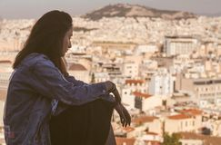 Young Greek girl on the background of the panorama of the city in the tourist area of Athens Anafiotika in Greece royalty free stock image
