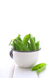 Young green peas in a metal colander. On a white background stock image