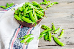 Young green peas in the pod, earthenware dish, rustic background. Raw Stock Photos