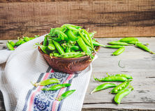 Young green peas in the pod, earthenware dish, rustic background. Raw Stock Photo