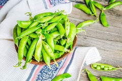 Young green peas in the pod, earthenware dish, rustic background. Raw Royalty Free Stock Photos