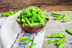 Young green peas in the pod, earthenware dish, rustic background. Raw Royalty Free Stock Photography