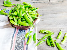 Young green peas in the pod, earthenware dish, rustic background. Raw Stock Photography