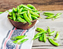 Young green peas in the pod, earthenware dish, rustic background. Raw Royalty Free Stock Image