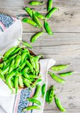 Young green peas in the pod, earthenware dish, rustic, top view. Young green peas in the pod, earthenware dish, rustic background, raw Stock Photo