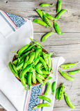 Young green peas in the pod, earthenware dish, rustic, top view. Young green peas in the pod, earthenware dish, rustic background, raw Royalty Free Stock Image