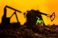 Young green plant in soil on background oil rocking machine.  stock photos