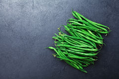 Young green or string beans on black stone table top view. Organic vegetarian food. Royalty Free Stock Photography