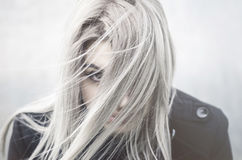 Young grey haired girl portrait in the wind. With covered face Stock Photos