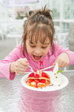 Young gril eating delicious strawberry waffle Stock Image