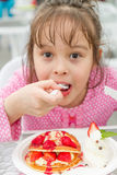 Young girl eating delicious strawberry waffle Stock Photos