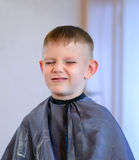 Young Grimacing Boy Getting Hair Cut Royalty Free Stock Photography
