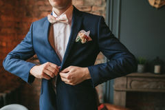 A young groom in a blue suit and a pink bow tie button his jacket against the backdrop of a brick wall and a fireplace Royalty Free Stock Images