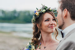Young groom and bride standing hugging on the background of the river Stock Photo