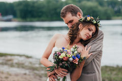 Young groom and bride standing hugging on the background of the river Stock Photography