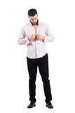 Young groom buttoning his pink shirt preparing for his wedding Stock Image