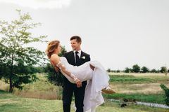 Young groom carrying his beautiful wife royalty free stock photo