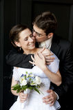 Young groom cuddle beautiful bride and kissing her. Young groom cuddle beautiful bride and kissing her on black royalty free stock image