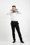 Young groom getting dressed adjusting bow tie looking away Royalty Free Stock Image