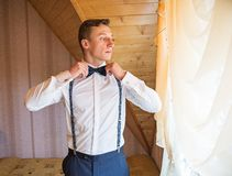 Young groom getting ready for the wedding ceremony. Standing by the window in a white shirt and suspenders and wears a bow tie Stock Photo