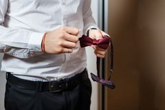 Young groom holding in his hands a red dotted bow-tie. Close-up of men`s wedding accessories. Young groom holding in his hands a red dotted bow-tie. Close-up of Stock Photo