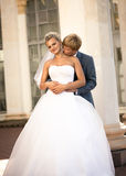 Young groom hugging smiling bride from back on the street Royalty Free Stock Photos