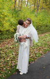 Young groom hugs his bride and kisses neck Stock Photography
