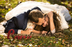 Young groom kissing beautiful bride in cheek lying on grass at p Royalty Free Stock Images