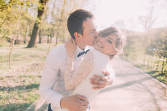 Young groom kissing beautiful bride on cheek in spring park Royalty Free Stock Images