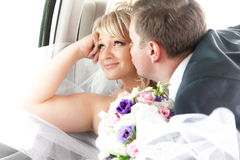 Young groom kissing smiling bride on backseat Stock Image