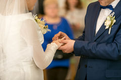 Young groom putting wedding ring on bride's finger. Closeup of young groom putting wedding ring on bride's finger royalty free stock photo